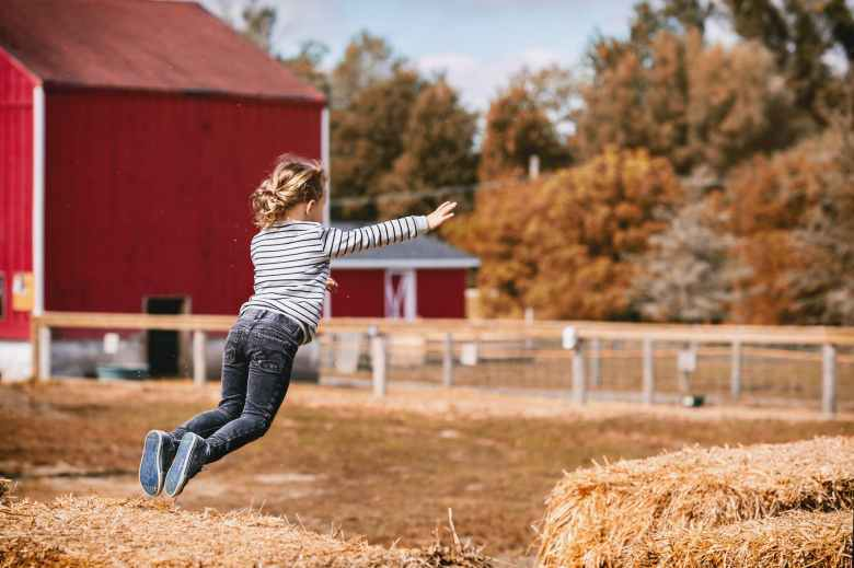 girl wearing white and black striped long sleeved shirt jumping outdoor